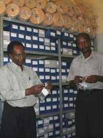 Mr. Longini Mtalo and Mr. Ingi Mayo arranging the shelf